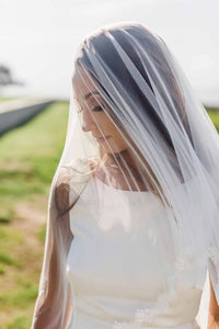 Close up of bride looking down wearing blusher style Lily drop veil featuring Venetian lace trim outside at her wedding