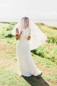 Bride wearing Lily drop style blusher wedding veil with Venetian lace trim by Mauve et Blush outside at her wedding