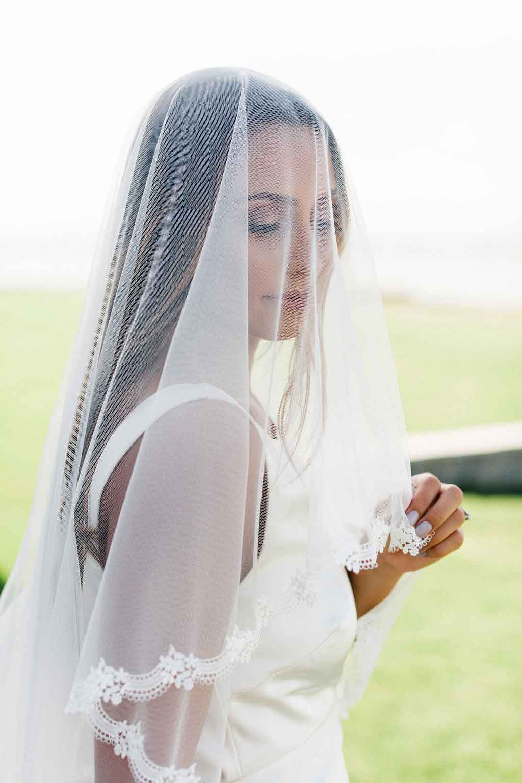 Bride wearing blusher style Lily drop veil by Mauve et Blush featuring Venetian lace trim outside at her wedding