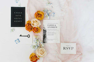 Detail view of Lily blusher veil with Venetian lace trim lying flat with wedding invitations and orange and cream roses