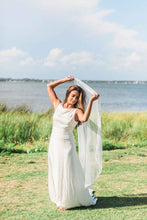 Cargar imagen en el visor de la galería, Bride lifting her Lily drop wedding veil with Venetian lace trim by Mauve et Blush outside with ocean in background