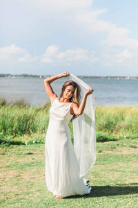 Bride lifting her Lily drop wedding veil with Venetian lace trim by Mauve et Blush outside with ocean in background