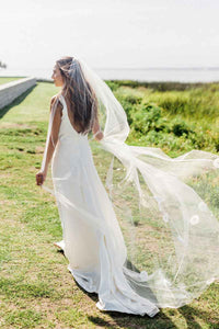 Bride stands outside with back turned wearing Poppy bridal veil by Mauve et Blush with organza flowers applique