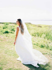Side portrait of bride standing outside in grass wearing Poppy bridal veil by Mauve et Blush on her wedding day