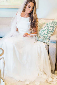 Bride sitting down wearing Poppy bridal veil by Mauve et Blush on her wedding day