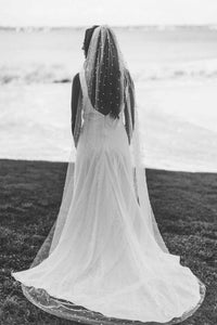 Bride with back turned wearing chapel length Zinnia pearl veil by Mauve et Blush