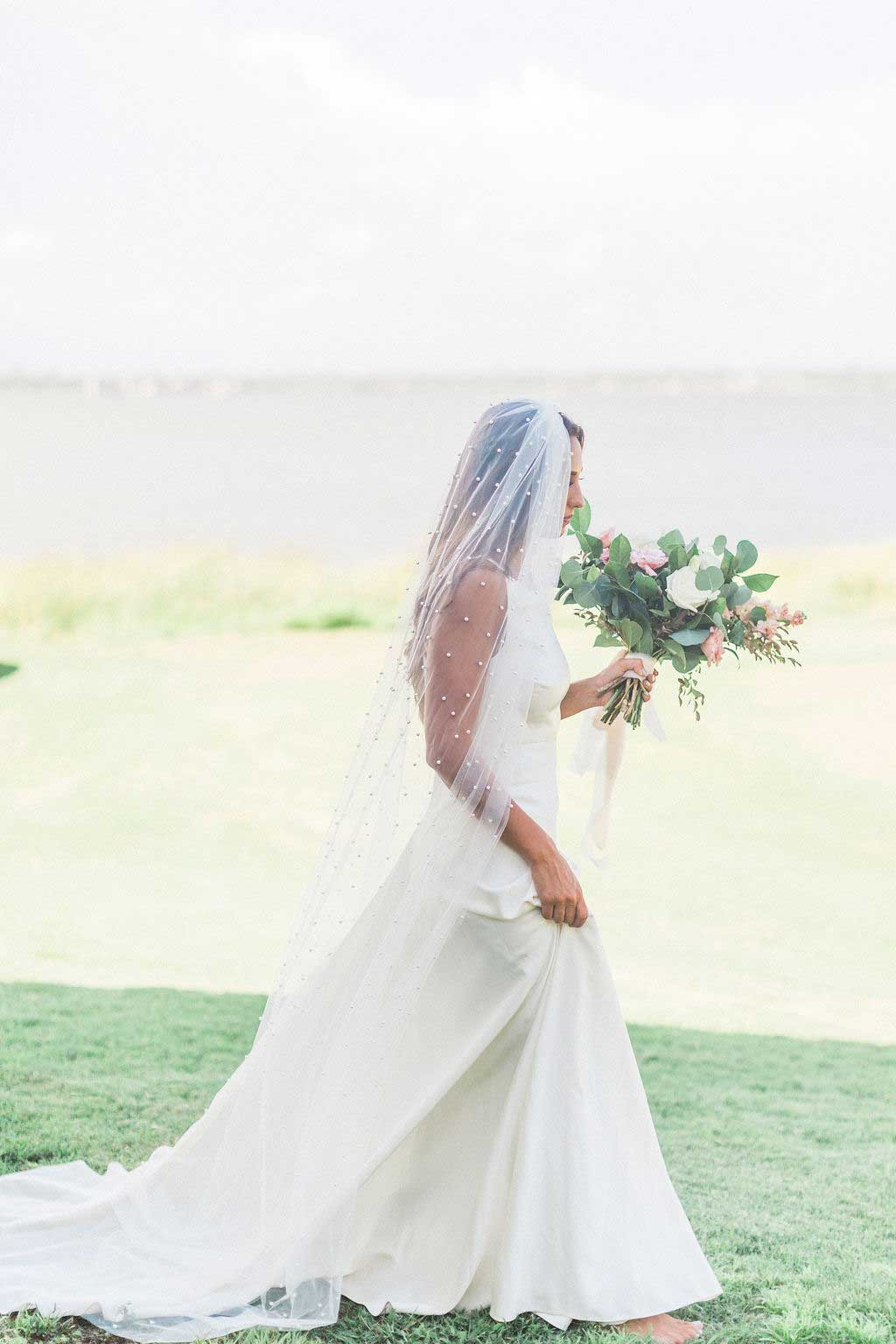 Bride walks outside in grass wearing chapel length Zinnia pearl bridal veil by Mauve et Blush and holding bouquet