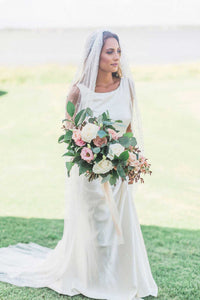 Bride stands outside in grass wearing Zinnia pearl bridal veil by Mauve et Blush while holding floral bouquet