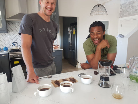Philip Snyman and Cecil Afrika standing at the kitchen counter when we did our first 18 coffee blend cupping, they are both laughing out of the surprise that our coffee dream might soon become a reality. There is bag of coffee, coffee grinder (Handground kickstarter project) and some cups on the counter.