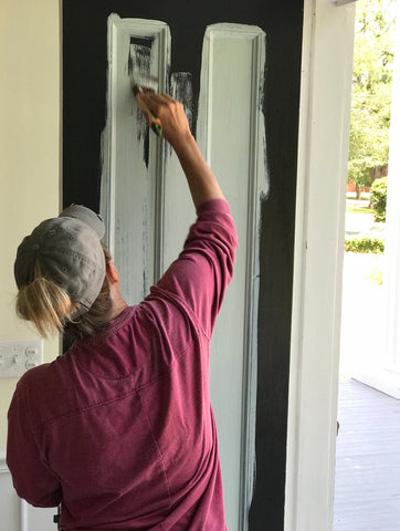 Pictured is a woman painting a door French Eggshell Fusion Mineral Paint. The door was previously black, but the new paint covers the old color.