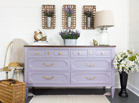 Pictured is a dresser painted with Divine Lavender Fusion Mineral Paint. It has gold drawer pulls. It is surrounded by floral decorations.