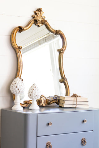 Pictured is a dresser painted with Sacred Sage Fusion Mineral Paint. On top of the dresser is a bound stack of books and two decorative sculptures, as well as a gold framed mirror.