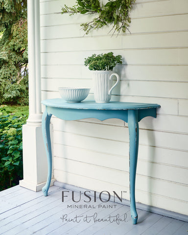 A round table has been cut in half and attached to the exterior wall of a house on the porch of the house. It has been painted with Heirloom Fusion Mineral Paint. On top of the table is a ceramic pot with plants in it and a ceramic bowl.
