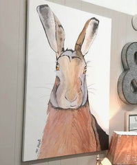 Pictured is a large sized canvas of the hare watercolor design hanging on a wall.