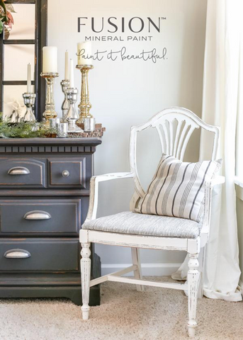 Pictured is a wooden chair with an upholstered seat. The chair is painted with Raw Silk Fusion Mineral Paint. On the chair is a pillow with grey and white stripes. Next to the chair is a dresser with candles and a mirror on top of it.