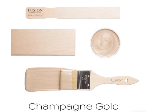 Pictured are 4 objects on a white background. The first is a wooden tester stick with Champagne Gold Metallic Fusion MIneral Paint. Next is a wood block also painted with Chapmagne Gold. Next is the bottom side of the lid of a container of Champagne Gold, showing the swirl of paint stuck to it. Finally, there is a paint brush brushing a thick coat of Champagne Gold onto the background.