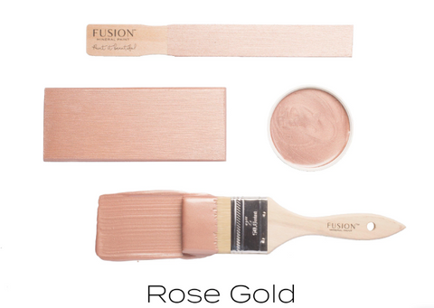 Pictured are 4 objects on a white background. The first object is a wooden tester stick with Rose Gold Metallic Fusion Mineral Paint painted onto it. The second is a wooden block also painted with Rose Gold. Next is the lid to a Rose Gold paint containter, displayed facing up so that the paint swirled on the inner surface is visible. Finally there is a paint brush brushing a streak of Rose Gold paint onto the white background.