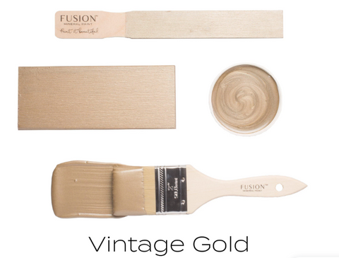 Pictured are 4 objects on a white background. The first object is a wooden tester stick with Vintage Gold Metallic Fusion Mineral Paint painted onto it. The second is a wooden block also painted with Vintage Gold. Next is the lid to a Vintage Gold paint containter, displayed facing up so that the paint swirled on the inner surface is visible. Finally there is a paint brush brushing a streak of Vintage Gold paint onto the white background.