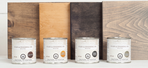 Pictured are four cans of Fusion Stain & Finishing Oil in front of four square pieces of wood which have been stained with the corresponding color of Stain & Finishing oil.