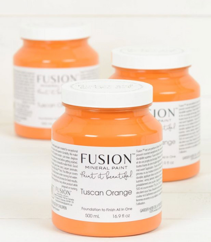 Pictured are three pint sized containers of Tuscan Orange Fusion Mineral Paint, positioned one in front of the other.