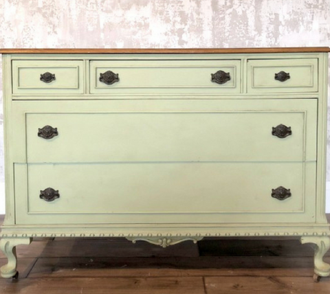 Pictured is a dresser painted with Upper Canada Green Fusion Mineral Paint. The top of the dresser has been left unpainted and the hardware is all black.