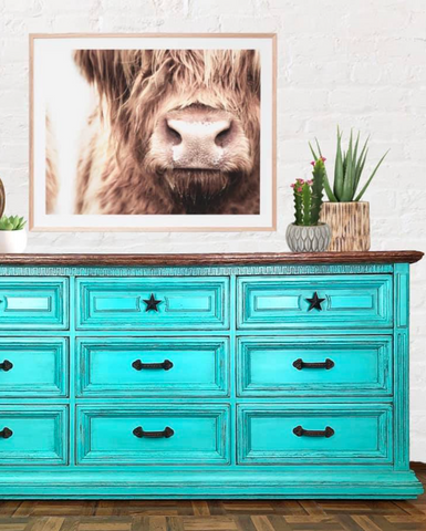 Pictured is a dresser painted with Azure Fusion Mineral Paint. On it are some potted plants and there is a framed picture of a cow hanging on the wall above it.
