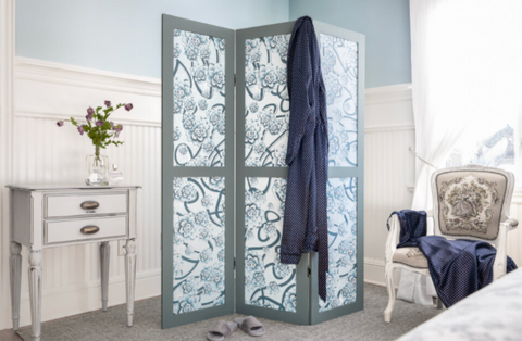 There is a folding room divider screen in the corner of a room, surrounded by bedroom furniture. The room divider is painted with Blue Pine Fusion Mineral Paint sold at The Hare & The Hart. The screen is done in a fabric with a pattern that matches the color of the gray-blue paint.