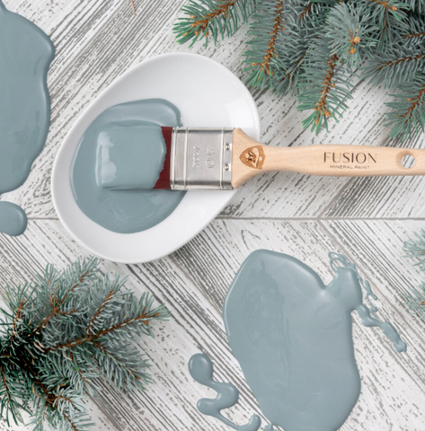 The picture is of a white plate with some Blue Pine Fusion Mineral Paint on it. There is a Staalmeester paintbrush dipped in the paint. It is surrounded by decorative tree branches.