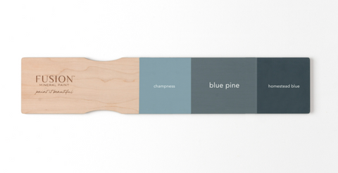There is a paint sample stick by Fusion Mineral Paint. There are three colors painted onto the stick. From left to right the colors are: Champness, Blue Pine, and Homestead Blue.