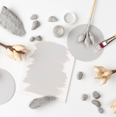 This picture is taken from above. On a white surface is a piece of paper, some rocks, and some dried flowers. All of the items have been either painted wholly or partially with Cobblestone Fusion Mineral Paint.