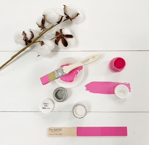 This picture is taken from above. There is a pint and a tester size of CUREiously Pink Fusion Mineral Paint. There are two other Fusion Mineral Paint tester sized paints. A swipe of CUREiously Pink has been painted onto the white surface. There is some cotton on the table as well.