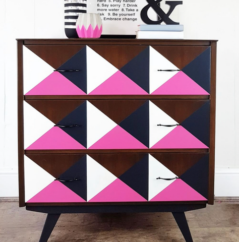 Pictured is a midcentury modern style dresser. The legs are painted with black Fusion Mineral Paint. The three drawers are each divided into a pattern of three squares. Each square is divided into four triangles, one natural wood, one white, one black, and one CUREiously Pink Fusion Mineral Paint.