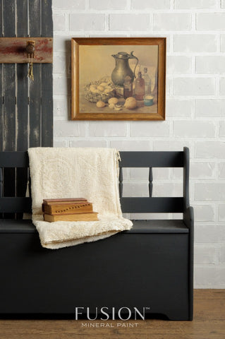 A bench painted with Ash Fusion Mineral Paint sits against a wall. There is a still life painting in a wooden frame hanging on the wall. A rustic wooden panel with coat hooks leans behind the bench and against the wall. There is a blanket draped across the bench with a stack of old books on top of it.