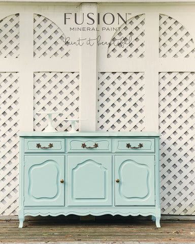 An ornate dresser is painted with Brook and sits in front of a wall of white latticework.