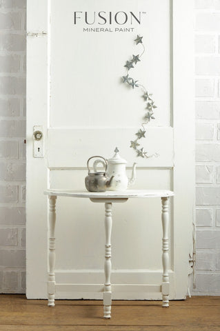 A small table painted in Casement Fusion Mineral Paint sits in front of a door also painted in Casement Fusion Mineral Paint. There are two teapots on top of the table and decorative metal stars on the door.