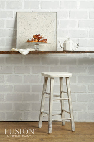 A bar stool painted with Champlain Fusion Mineral Paint sits in front of a bar. On top of the bar is an old ceiling tile also painted with Champlain, a plate of cinnamon rolls, and a teapot.