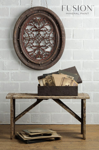 A rustic bench is pictured. On the floor below it is a pile of old papers and photographs. On top of the bench is a basket painted in Chocolate Fusion Mineral Paint. In the basket are more old papers and photographs. On the wall is a hanging metal decoration.