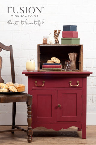 A small cabinet painted with Cranberry Fusion Mineral Paint is pictured. Next to it is a chair with a plate of pastries on it. There are various boxes and books on top of the cabinet for decoration.