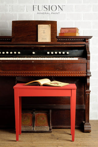 Pictured is a piano bench painted with Fort York Red Fusion Mineral Paint with an open book on top of it. It sits in front of an old piano.