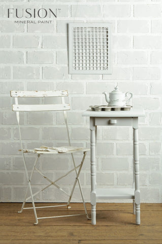 Pictured is an old folding chair painted with Lamp White Fusion Mineral Paint. There is also a small side table next to the chair painted with Lamp White. On top of the table is a muffin tin and a teapot.