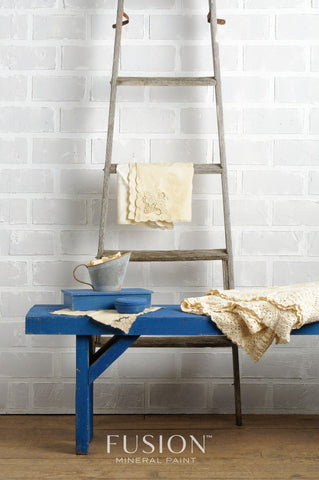 Pictured is a wooden bench painted with Liberty Blue Fusion Mineral Paint. On top of it is a folded cream blanket and some other decorative items painted in Liberty Blue. Behind the bench is a ladder with a cream blanket draped over one of the rungs.