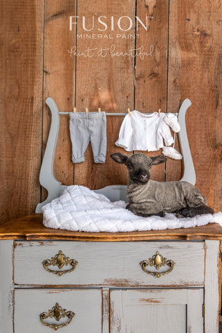 Pictured is an old changing table painted with Little Lamb Fusion Mineral Paint. The top of the changing table is gold. It has a towel laying across it and on top of that towel is a very realistic sculpture of a lamb laying down. On the back of the dresser is a clothes line with baby clothes clipped to it.