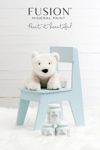 Pictured is a children's sized modern wooden chair painted with Little Whale Fusion Mineral Paint. It's sitting on a fluffy white rug with a stack of 3 pints of Little Whale. On top of the chair sits a white teddy bear.