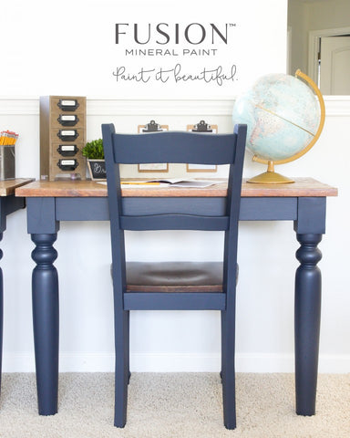 Pictured is a desk painted with Midnight Blue. There is a chair at the desk also painted with Midnight Blue. On the desk are various decorations, including a globe.