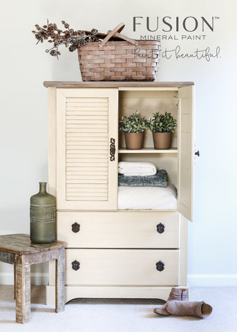 Pictured is a dresser painted with Plaster Fusion Mineral Paint. The top of the dresser is unpainted and has an old basket with dried cotton inside it. One door of the dresser is open. Inside are two potted plants and a stack of linens. Next to the dresser is a small wooden table with an antique jug on it and a pair of boots.