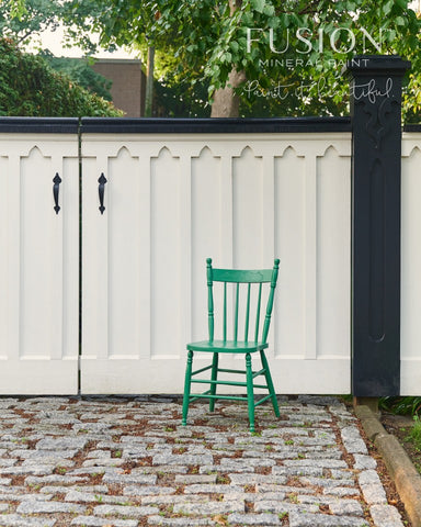 Pictured is a wooden chair painted with Park Bench Fusion Mineral Paint. The chair sits on a cobblestone driveway in front of an ornate white and black painted wooden gate.