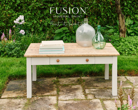 Pictured is a coffee table painted with Putty Fusion Mineral Paint. On top of the table is a stack of books and some antique glass bottles. The table sits outside.