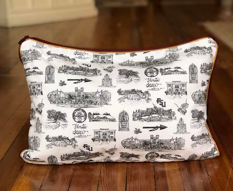There is a lumbar pillow covered with Toile of FSU fabric. The Toile of FSU pattern is black and white. The border of the pillow is garnet and gold piping.