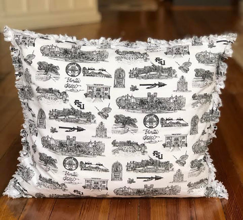 Pictured is a square pillow covered with Toile of FSU black and white patterned fabric. The edges of the pillow are frayed.