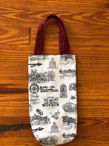 Pictured is a fabric wine tote. The body of the bag is made of Toile of FSU black and white fabric. The two handles are made of garnet fabric. The tote lays on a wood floor.
